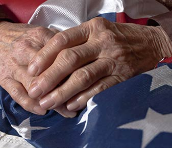 Older Hands on American Flag